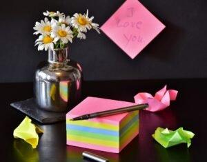 vaso com flores e um bloquinho com mensagem para o Dia dos Namorados