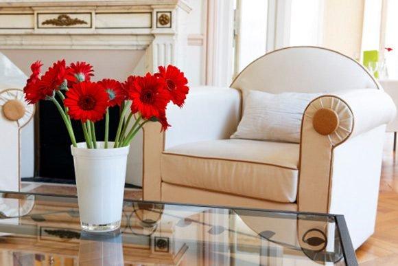 arranjo de flores vermelhas na mesa com a sala o fundo